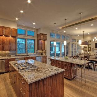 Foto de cocina clásica renovada, abierta, con armarios con paneles empotrados, puertas de armario de madera en tonos medios y electrodomésticos de acero inoxidable
