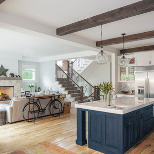 Large farmhouse eat-in kitchen designs - Eat-in kitchen - large farmhouse single-wall light wood floor and brown floor eat-in kitchen idea in Denver with shaker cabinets, white cabinets, quartzite countertops, stainless steel appliances, an island and white countertops
