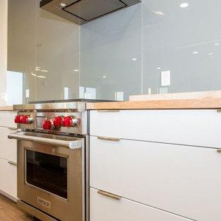 カルガリーの中くらいのコンテンポラリースタイルのおしゃれなキッチン (アンダーカウンターシンク、フラットパネル扉のキャビネット、白いキャビネット、木材カウンター、グレーのキッチンパネル、ガラス板のキッチンパネル、シルバーの調理設備、クッションフロア) の写真