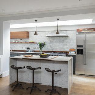 ロンドンの中サイズのエクレクティックスタイルのおしゃれなキッチン (アンダーカウンターシンク、フラットパネル扉のキャビネット、中間色木目調キャビネット、大理石カウンター、グレーのキッチンパネル、大理石の床、シルバーの調理設備の、無垢フローリング、茶色い床、グレーのキッチンカウンター) の写真