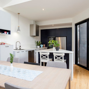 Photo of a small contemporary single-wall eat-in kitchen in Melbourne with an undermount sink, stainless steel appliances, medium hardwood floors, with island, brown floor and white benchtop.
