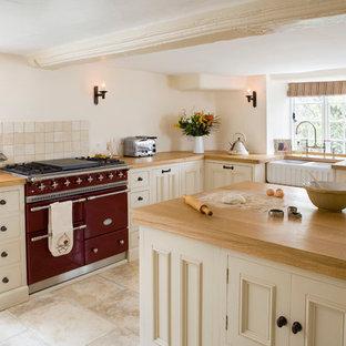 Aménagement d'une petit cuisine montagne fermée avec un évier de ferme, des portes de placard beiges, un plan de travail en bois, un sol en travertin et une péninsule.