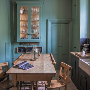 Photo of a small country l-shaped eat-in kitchen in Gloucestershire with shaker cabinets, green cabinets, wood benchtops, limestone floors, a drop-in sink, black splashback, stone tile splashback, coloured appliances and no island.