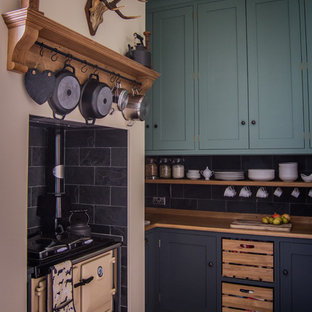 This is an example of a small traditional l-shaped eat-in kitchen in Gloucestershire with shaker cabinets, wood benchtops, black splashback, stone tile splashback, coloured appliances, limestone floors, a drop-in sink, green cabinets and no island.