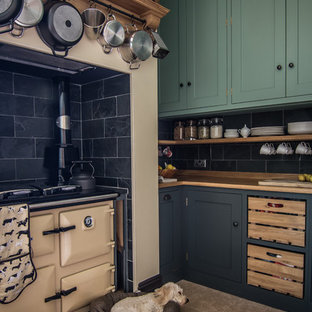 Photo of a small contemporary l-shaped eat-in kitchen in Gloucestershire with a drop-in sink, shaker cabinets, green cabinets, wood benchtops, black splashback, stone tile splashback, coloured appliances, limestone floors and no island.