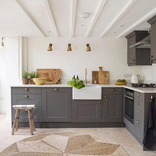Inredning av ett lantligt vit vitt l-kök, med en rustik diskho, skåp i shakerstil, grå skåp, bänkskiva i kvartsit, rostfria vitvaror, kalkstensgolv och beiget golv