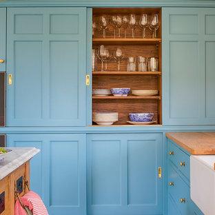 Esempio di una cucina con lavello stile country, ante blu, top in legno, elettrodomestici da incasso, pavimento in terracotta, isola, top marrone e ante in stile shaker