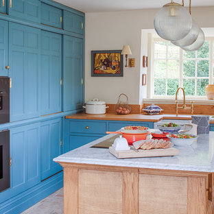 Traditional l-shaped kitchen in Gloucestershire with a belfast sink, beaded cabinets, blue cabinets, wood worktops, stainless steel appliances, an island, beige floors and brown worktops.