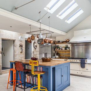 Design ideas for a farmhouse kitchen in Gloucestershire with blue cabinets, wood worktops, an island, recessed-panel cabinets, white floors and white appliances.