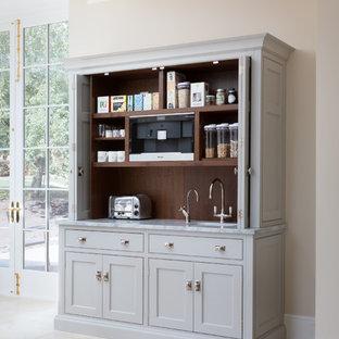 Cette photo montre une grande cuisine chic avec un placard à porte shaker, des portes de placard grises, une crédence marron, une crédence en fenêtre, un sol beige et un plan de travail gris.