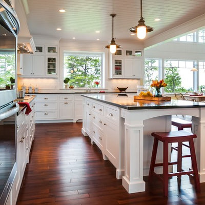 Eat-in kitchen - large craftsman u-shaped medium tone wood floor eat-in kitchen idea in Other with an undermount sink, shaker cabinets, white cabinets, granite countertops, white backsplash, ceramic backsplash, stainless steel appliances and an island