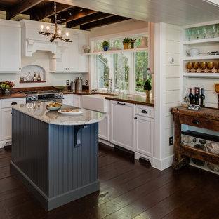 Bild på ett avskilt, litet rustikt l-kök, med en rustik diskho, träbänkskiva, vita skåp, luckor med infälld panel, rostfria vitvaror, vitt stänkskydd, stänkskydd i trä, mörkt trägolv, en köksö och brunt golv