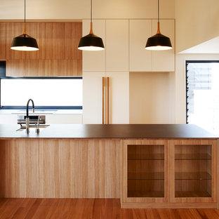 Aménagement d'une grande cuisine américaine parallèle avec un évier encastré, des portes de placard en bois clair, un plan de travail en carrelage, une crédence en fenêtre, un électroménager en acier inoxydable, un sol en bois clair, un îlot central et un plan de travail gris.