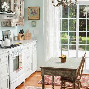Ejemplo de cocina comedor lineal, romántica, con armarios tipo vitrina, puertas de armario con efecto envejecido y electrodomésticos blancos
