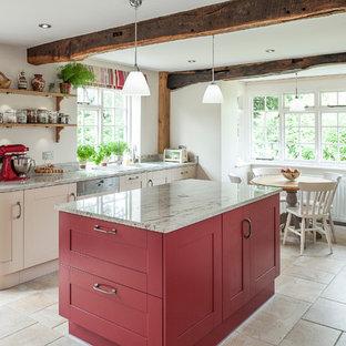Große Landhaus Wohnküche mit Doppelwaschbecken, roten Schränken, Granit-Arbeitsplatte, Elektrogeräten mit Frontblende, Porzellan-Bodenfliesen und Kücheninsel in Kent
