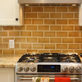 Ispirazione per una piccola cucina ad U eclettica chiusa con lavello sottopiano, ante in stile shaker, ante bianche, top in granito, paraspruzzi giallo, paraspruzzi con piastrelle in ceramica, elettrodomestici in acciaio inossidabile e pavimento in legno massello medio