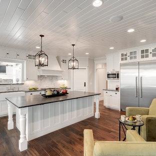 ミネアポリスの中くらいのトラディショナルスタイルのおしゃれなキッチン (エプロンフロントシンク、落し込みパネル扉のキャビネット、白いキャビネット、白いキッチンパネル、サブウェイタイルのキッチンパネル、シルバーの調理設備、ソープストーンカウンター、濃色無垢フローリング、茶色い床) の写真