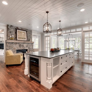 Large transitional enclosed kitchen appliance - Large transitional single-wall dark wood floor and brown floor enclosed kitchen photo in Minneapolis with a farmhouse sink, recessed-panel cabinets, white cabinets, stainless steel appliances, soapstone countertops and an island