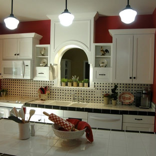 This is an example of a small country single-wall eat-in kitchen in Louisville with a double-bowl sink, shaker cabinets, white cabinets, tile benchtops, multi-coloured splashback, ceramic splashback, white appliances, dark hardwood floors and with island.