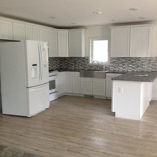 Design ideas for a small traditional u-shaped eat-in kitchen in Detroit with a farmhouse sink, white cabinets, granite benchtops, grey splashback, glass tile splashback, white appliances, vinyl floors and a peninsula.