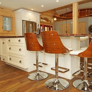 Mittelgroße Rustikale Wohnküche in L-Form mit Unterbauwaschbecken, Schrankfronten im Shaker-Stil, weißen Schränken, Granit-Arbeitsplatte, Küchenrückwand in Braun, Rückwand aus Holz, Küchengeräten aus Edelstahl, braunem Holzboden, Kücheninsel, braunem Boden und oranger Arbeitsplatte in Sonstige