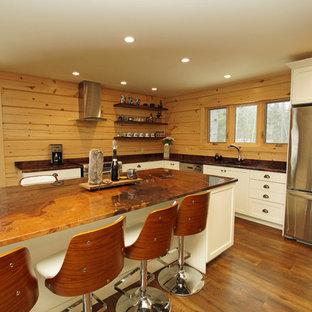 Rustik inredning av ett mellanstort orange oranget kök, med en undermonterad diskho, skåp i shakerstil, vita skåp, granitbänkskiva, brunt stänkskydd, stänkskydd i trä, rostfria vitvaror, mellanmörkt trägolv, en köksö och brunt golv