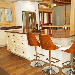 This is an example of a mid-sized country l-shaped eat-in kitchen in Other with an undermount sink, shaker cabinets, white cabinets, granite benchtops, brown splashback, timber splashback, stainless steel appliances, medium hardwood floors, with island, brown floor and orange benchtop.