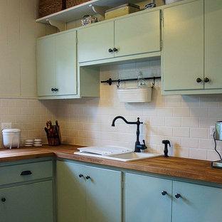 オタワの小さいカントリー風おしゃれなキッチン (ダブルシンク、フラットパネル扉のキャビネット、緑のキャビネット、木材カウンター、白いキッチンパネル、サブウェイタイルのキッチンパネル、シルバーの調理設備の、塗装フローリング、アイランドなし) の写真