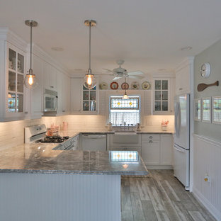This is an example of a small beach style l-shaped kitchen in Philadelphia with a farmhouse sink, shaker cabinets, white cabinets, marble benchtops, white splashback, subway tile splashback, white appliances, ceramic floors and with island.