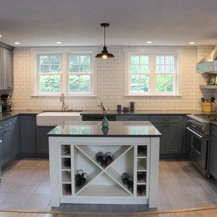 Design ideas for a small arts and crafts u-shaped eat-in kitchen in Other with a farmhouse sink, shaker cabinets, blue cabinets, quartz benchtops, white splashback, subway tile splashback, stainless steel appliances, ceramic floors, with island and brown floor.