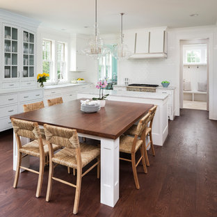 Design ideas for a large beach style eat-in kitchen in Minneapolis with white cabinets, marble benchtops, white splashback, ceramic splashback, stainless steel appliances, dark hardwood floors, with island, brown floor, glass-front cabinets and grey benchtop.