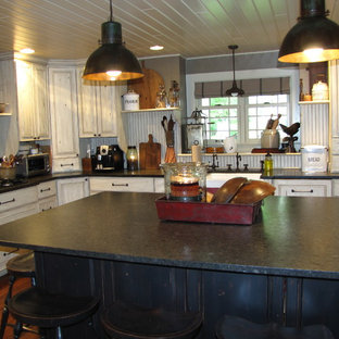Design ideas for a large traditional u-shaped separate kitchen in Other with a farmhouse sink, raised-panel cabinets, beige cabinets, granite benchtops, beige splashback, black appliances, dark hardwood floors and with island.