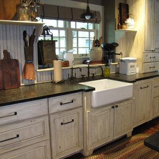 他の地域の大きいシャビーシック調のおしゃれなキッチン (エプロンフロントシンク、レイズドパネル扉のキャビネット、ベージュのキャビネット、御影石カウンター、ベージュキッチンパネル、濃色無垢フローリング、木材のキッチンパネル、白い調理設備、茶色い床) の写真