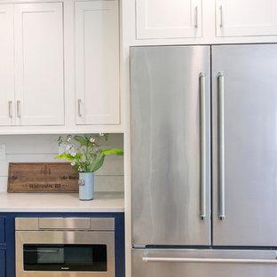Geschlossene, Mittelgroße Landhausstil Küche in U-Form mit Landhausspüle, Kassettenfronten, blauen Schränken, Quarzwerkstein-Arbeitsplatte, Küchenrückwand in Weiß, Rückwand aus Keramikfliesen, Küchengeräten aus Edelstahl, Linoleum, braunem Boden und grauer Arbeitsplatte in Milwaukee