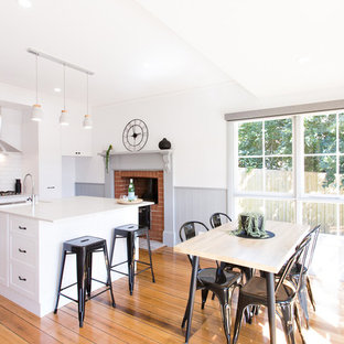 Inspiration for a scandinavian single-wall eat-in kitchen in Other with a farmhouse sink, shaker cabinets, white cabinets, white splashback, stainless steel appliances, medium hardwood floors, an island, brown floor and white benchtop.