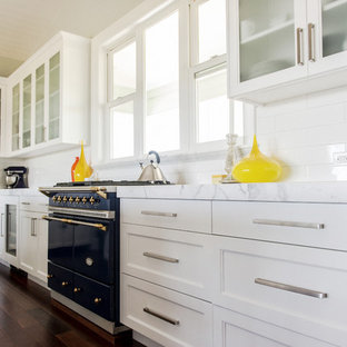 Small beach style open concept kitchen appliance - Small coastal single-wall dark wood floor open concept kitchen photo in Hawaii with an undermount sink, shaker cabinets, white cabinets, marble countertops, white backsplash, ceramic backsplash, paneled appliances and an island