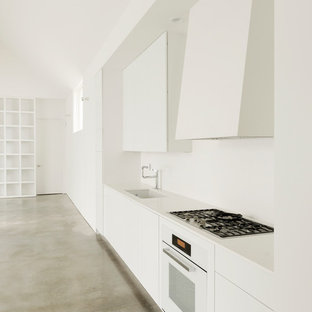 Mid-sized contemporary single-wall open plan kitchen in Houston with an undermount sink, flat-panel cabinets, white cabinets, white appliances, concrete floors, solid surface benchtops, no island and white splashback.