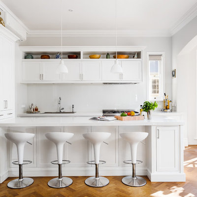 Example of a mid-sized transitional galley medium tone wood floor and brown floor kitchen design in Perth with white cabinets, solid surface countertops, glass sheet backsplash, stainless steel appliances, a drop-in sink, shaker cabinets and a peninsula