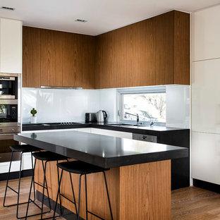 Retro Küche in L-Form mit flächenbündigen Schrankfronten, hellbraunen Holzschränken, Küchenrückwand in Weiß, Glasrückwand, braunem Holzboden und Kücheninsel in Perth