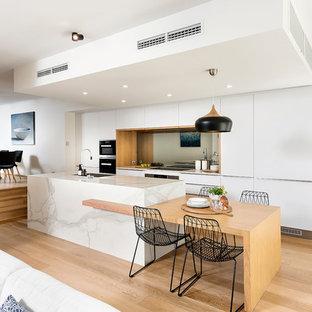 Nordisk inredning av ett stort kök, med en enkel diskho, släta luckor, vita skåp, spegel som stänkskydd, svarta vitvaror, ljust trägolv och en köksö