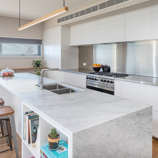 Inspiration for a contemporary galley open plan kitchen in Perth with a double-bowl sink, flat-panel cabinets, white cabinets, stainless steel benchtops, metallic splashback, metal splashback, stainless steel appliances, light hardwood floors, with island and grey benchtop.