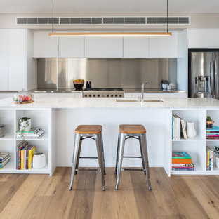 Photo of a contemporary single-wall open plan kitchen in Perth with flat-panel cabinets, white cabinets, marble benchtops, stainless steel appliances, with island, white benchtop, a double-bowl sink, metallic splashback, light hardwood floors and beige floor.
