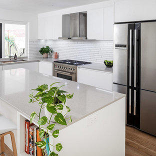 Contemporary kitchen remodeling - Trendy light wood floor kitchen photo in Perth with an undermount sink, white cabinets, quartz countertops, white backsplash, ceramic backsplash, stainless steel appliances and an island