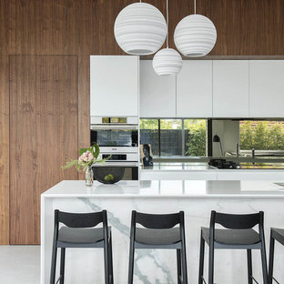 This is an example of a contemporary galley kitchen in Perth with an undermount sink, flat-panel cabinets, medium wood cabinets, mirror splashback, stainless steel appliances, with island, white floor and white benchtop.