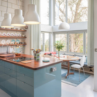 Medium sized scandi kitchen/diner in Oxfordshire with a submerged sink, flat-panel cabinets, blue cabinets, wood worktops, an island and grey floors.