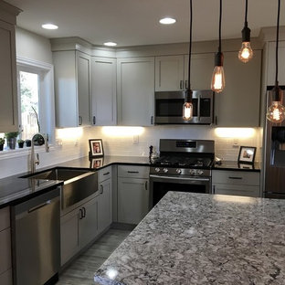 Inspiration for a mid-sized country l-shaped separate kitchen in Denver with a farmhouse sink, shaker cabinets, beige cabinets, quartz benchtops, white splashback, stainless steel appliances, vinyl floors, with island, subway tile splashback and grey floor.