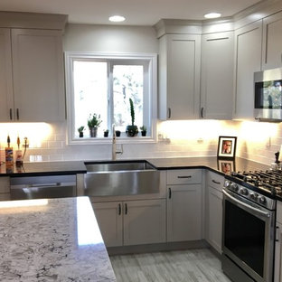 Photo of a mid-sized country l-shaped separate kitchen in Denver with a farmhouse sink, shaker cabinets, beige cabinets, quartz benchtops, white splashback, stainless steel appliances, vinyl floors, with island, subway tile splashback and grey floor.