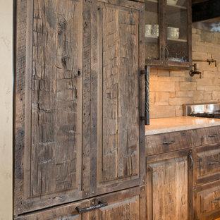 他の地域の広いラスティックスタイルのおしゃれなキッチン (シェーカースタイル扉のキャビネット、ヴィンテージ仕上げキャビネット、ライムストーンカウンター、茶色いキッチンパネル、石タイルのキッチンパネル、カラー調理設備、無垢フローリング、茶色い床) の写真