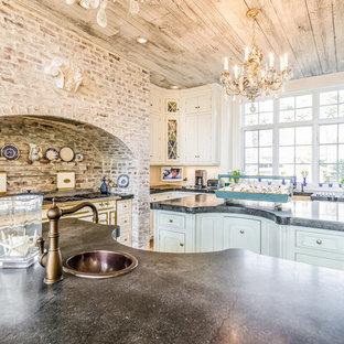 Foto di una cucina stile shabby di medie dimensioni con lavello stile country, ante con riquadro incassato, pavimento in legno massello medio, 2 o più isole, ante bianche, top in cemento, pavimento marrone e top nero