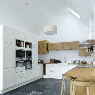 Photo of a medium sized country u-shaped kitchen in Other with a belfast sink, recessed-panel cabinets, white cabinets, wood worktops, stainless steel appliances, a breakfast bar, black floors and beige worktops.